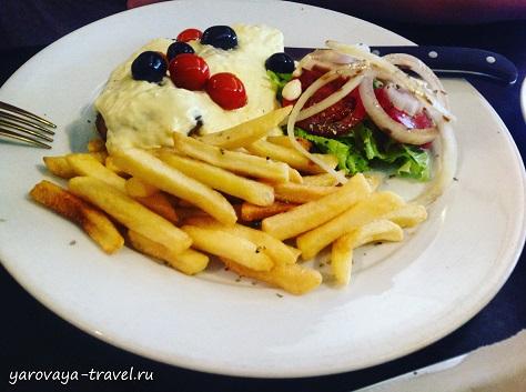Мясной стейк под сливочным соусом с картофелем и салатом.