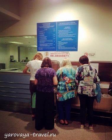 Женщины стоят и заполняют анкеты.