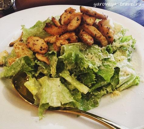 Теплый салат с курицей, сочными листьями салата, соусом и тертым сыром.