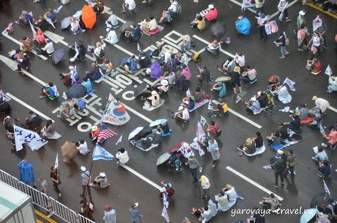 Вид из окна отеля на демонстрантов, сидящих на асфальте.