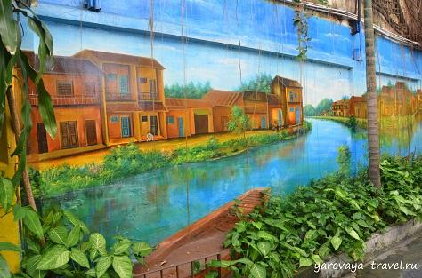 В переулке на стенах вы увидите виды вьетнамского города ХойАн.